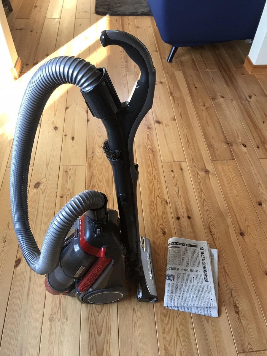 ブラシ付き掃除機と新聞紙
